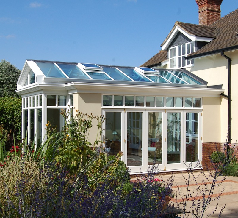 An bespoke orangery extension in Barrington, Cambridgeshire with folding doors, roof windows, thermal glass and a rendered finish